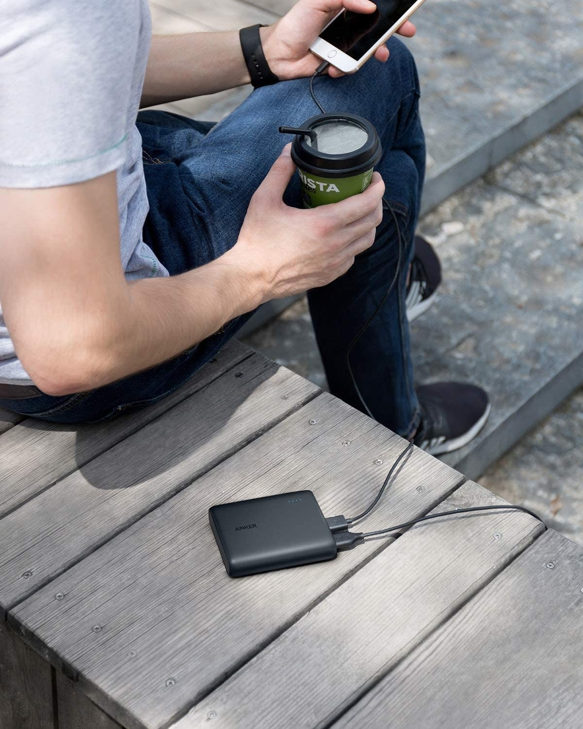 person sitting on a bench with their portable charger