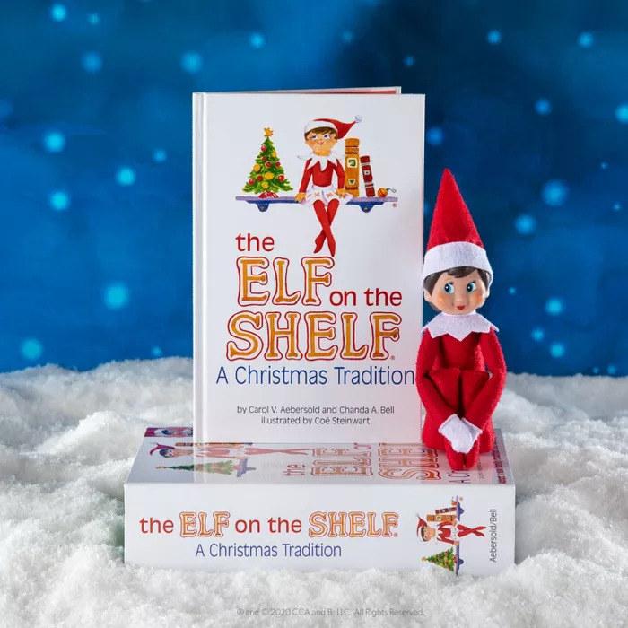 """""""The Elf on the Shelf"""" by Chanda Bell sitting with the box and accompanying elf doll"""