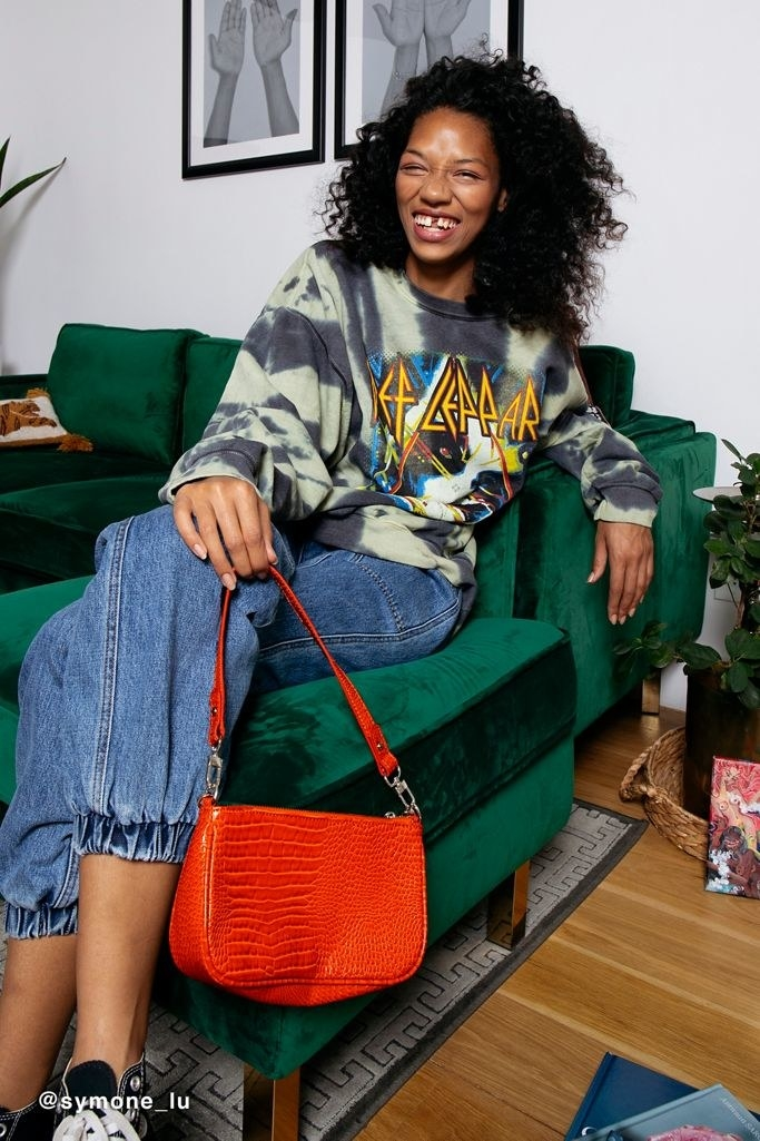 a model lounges on a velvet couch holding the rosie chain baguette in orange