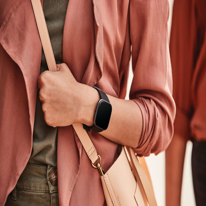 person wearing a black fitbit versa 2 smartwatch