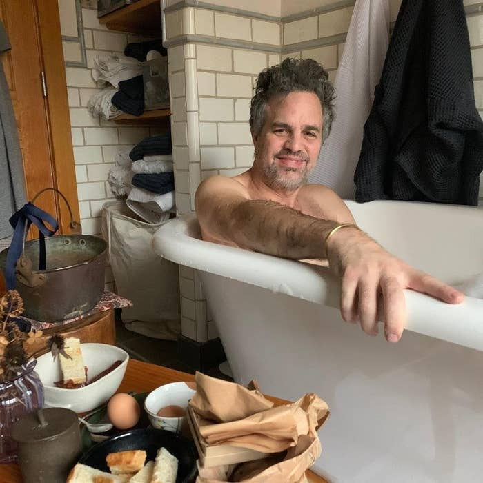 Mark smiling while in the bath next to a side table holding plates of eggs and bread