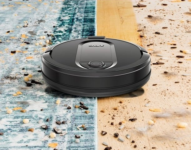 shark robot vacuum cleaning up debris off of a hardwood floor and a rug at the same time