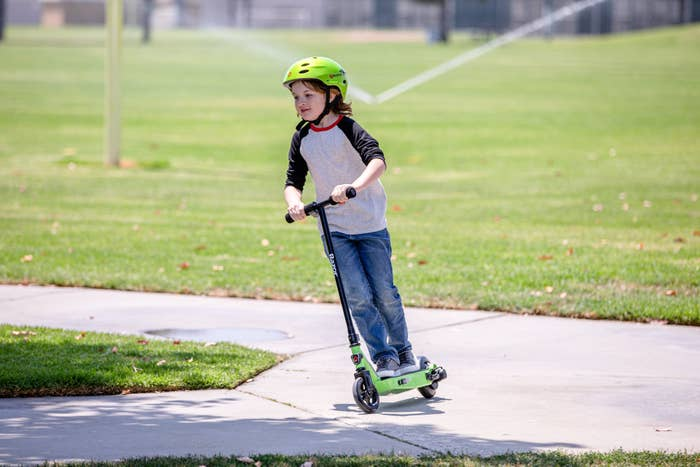 child riding a green razor electric scooter in a park