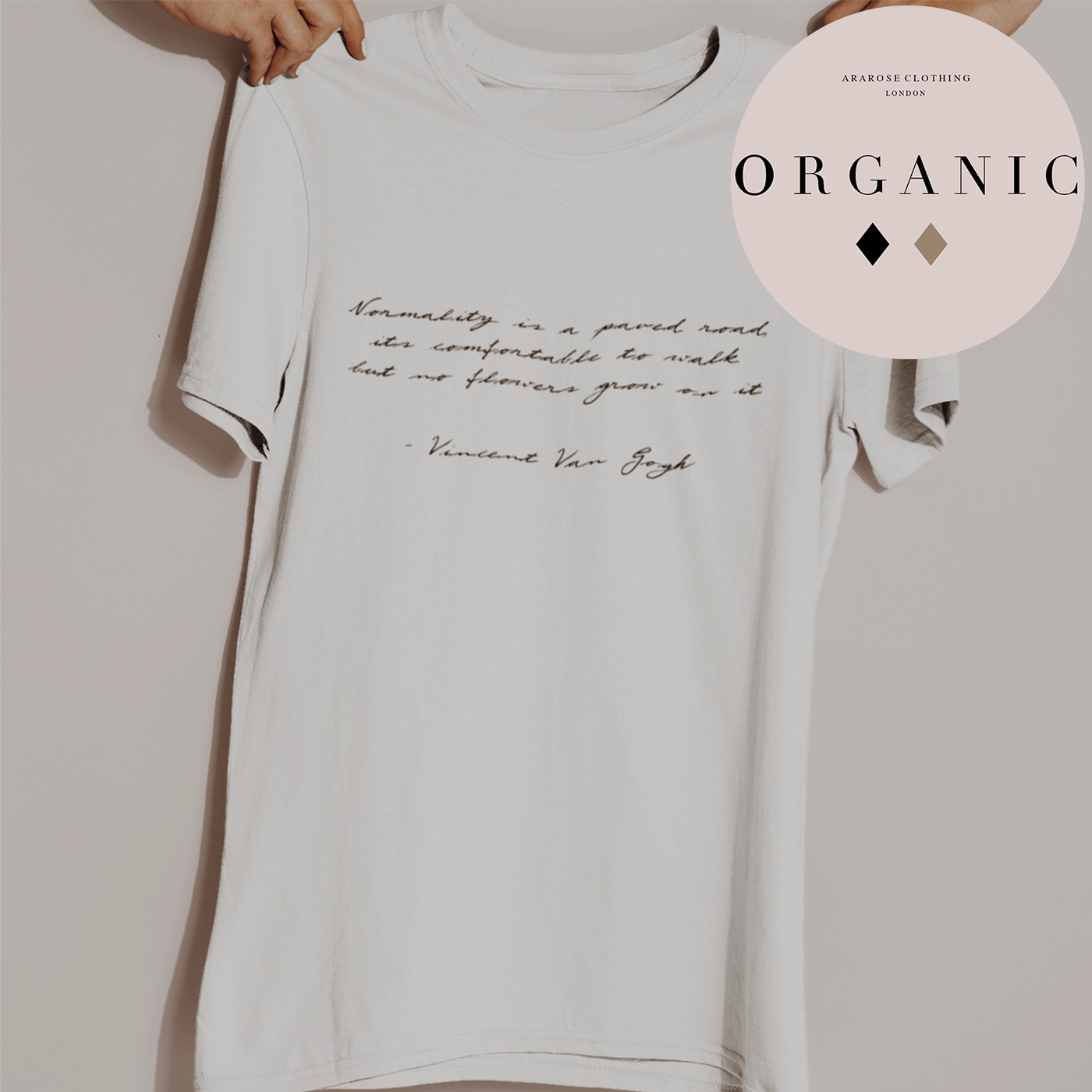 a hand holds up the organic statement tee