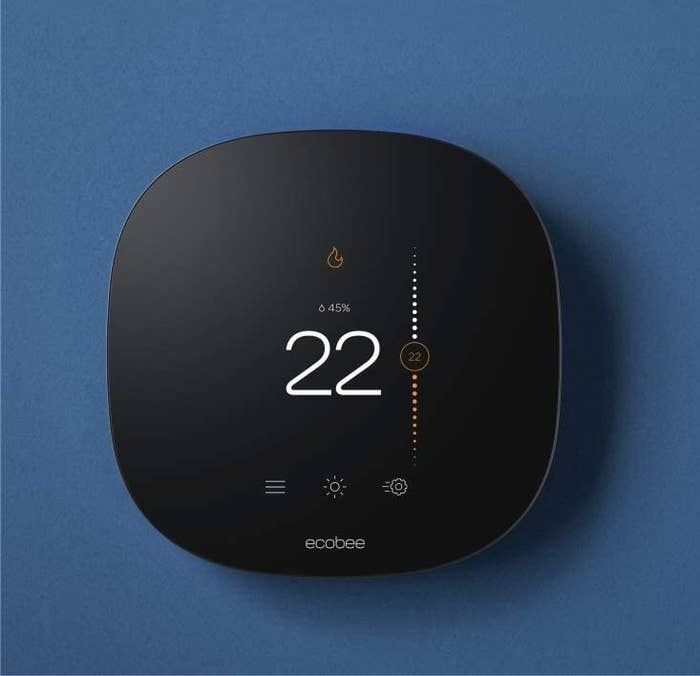 A smart thermostat mounted on a colourful wall