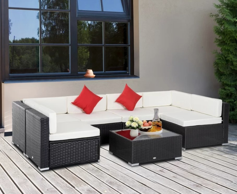 Black outdoor sectional with white cushions, red pillows