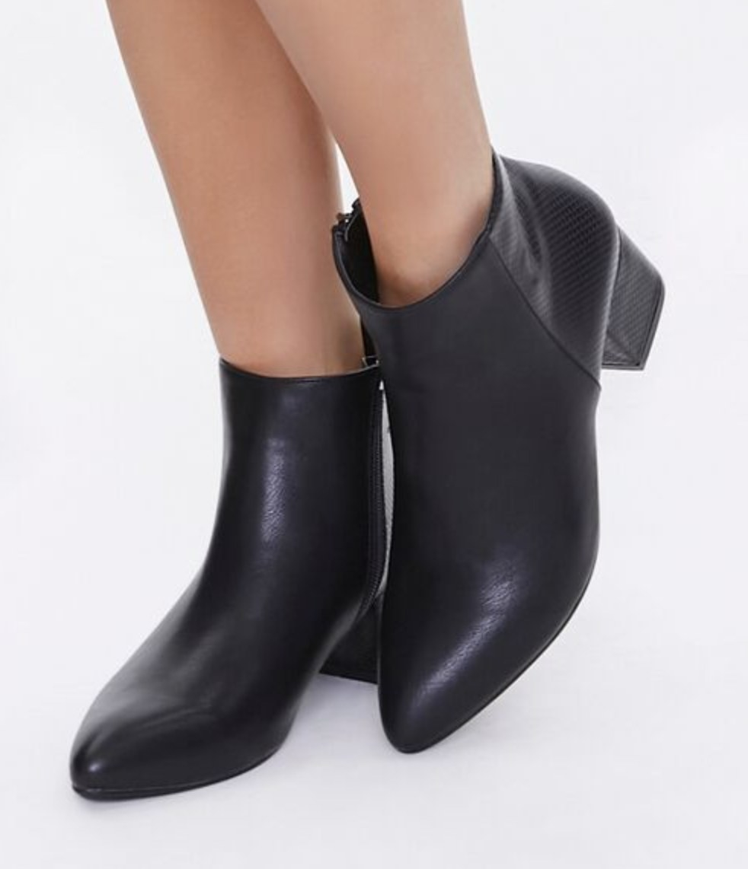 Model is wearing black faux leather booties