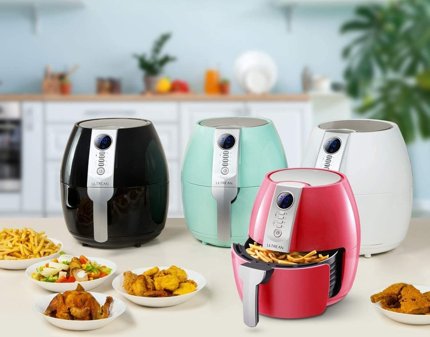 A set of four air fryers in varying colours arranged on a counter
