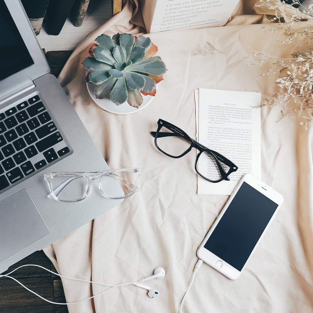 A pair of glasses on a desk next to a cell phone and a computer