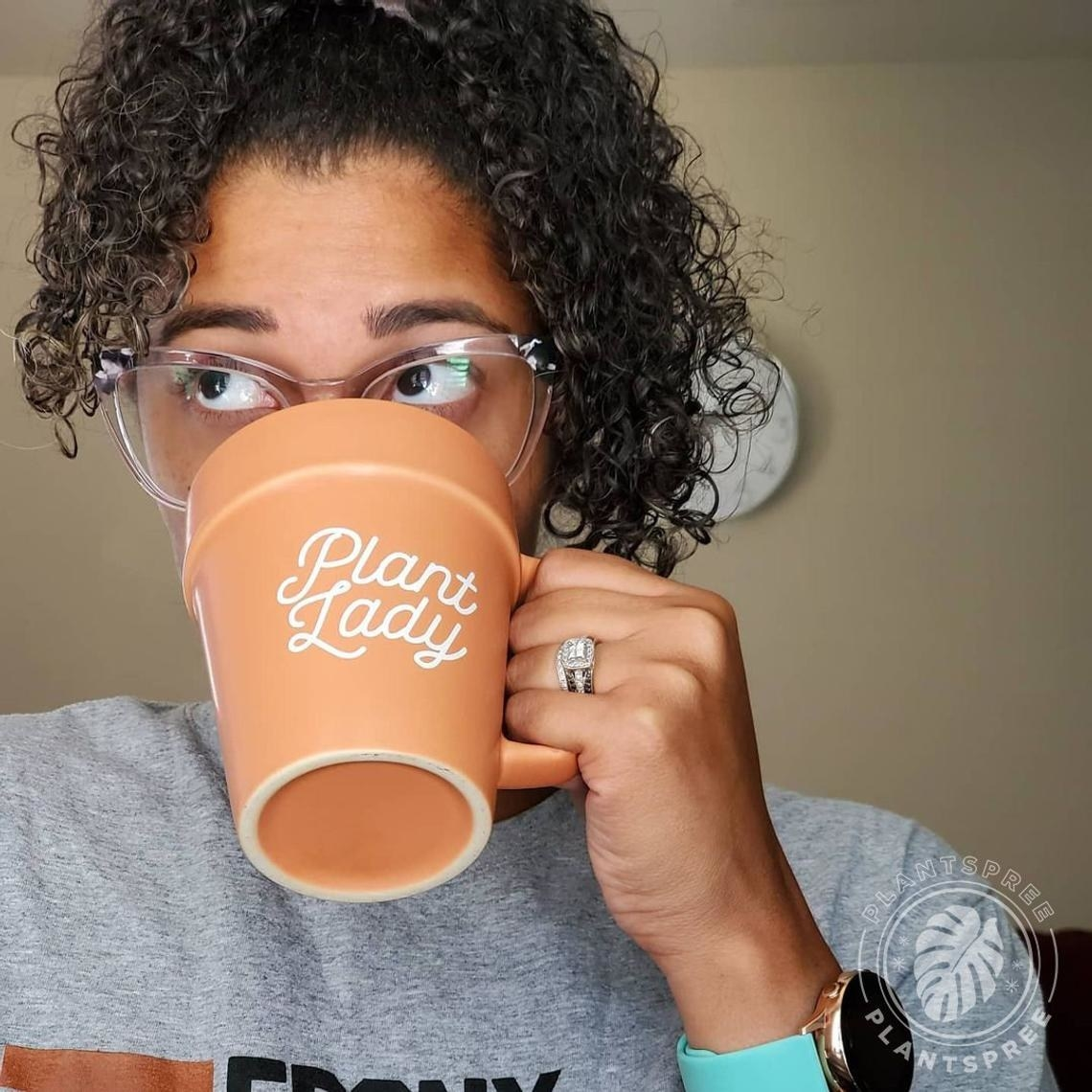 A person drinking out the plant lady mug