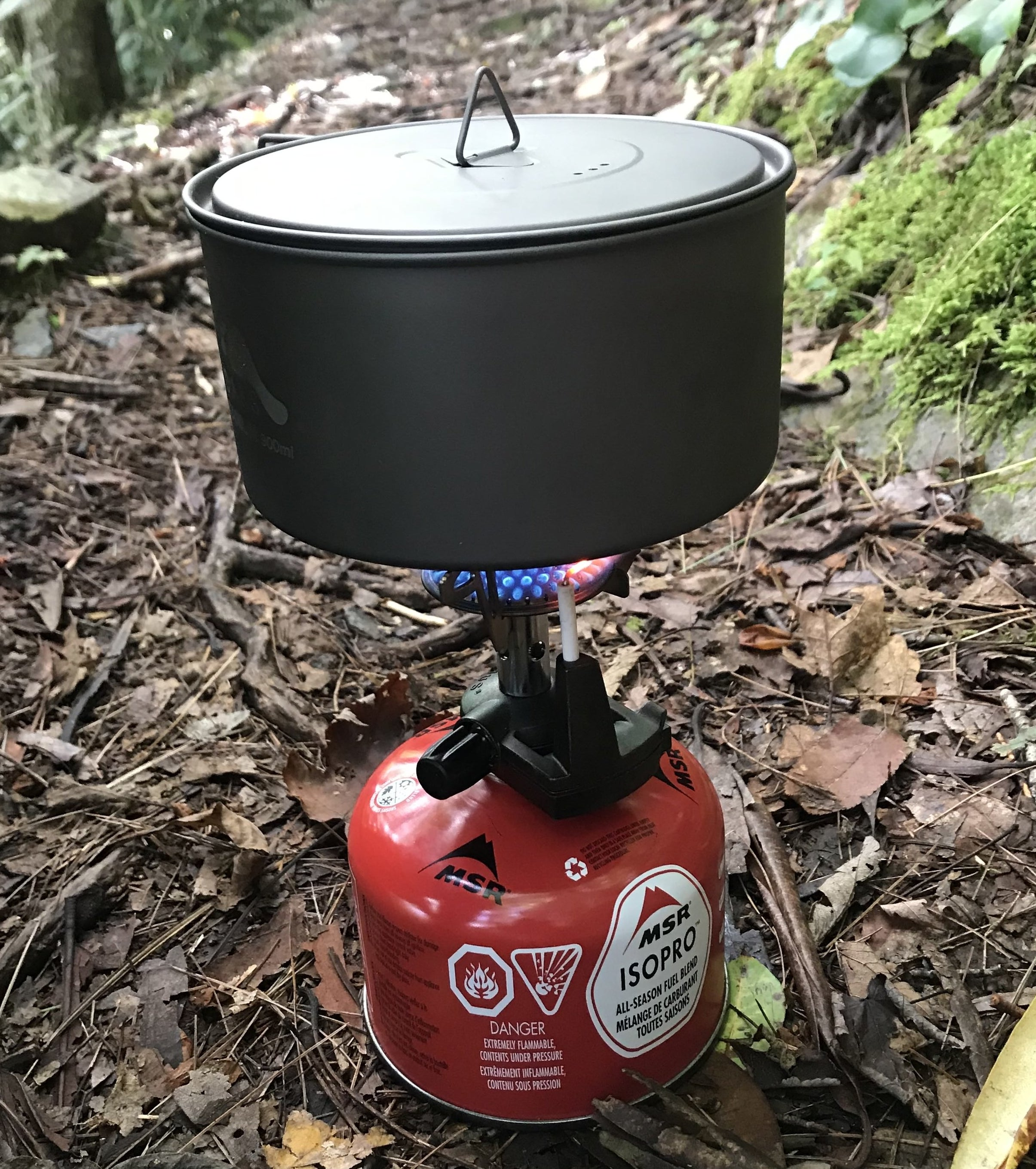 the writer's pot and lid sitting on a small lit camp stove