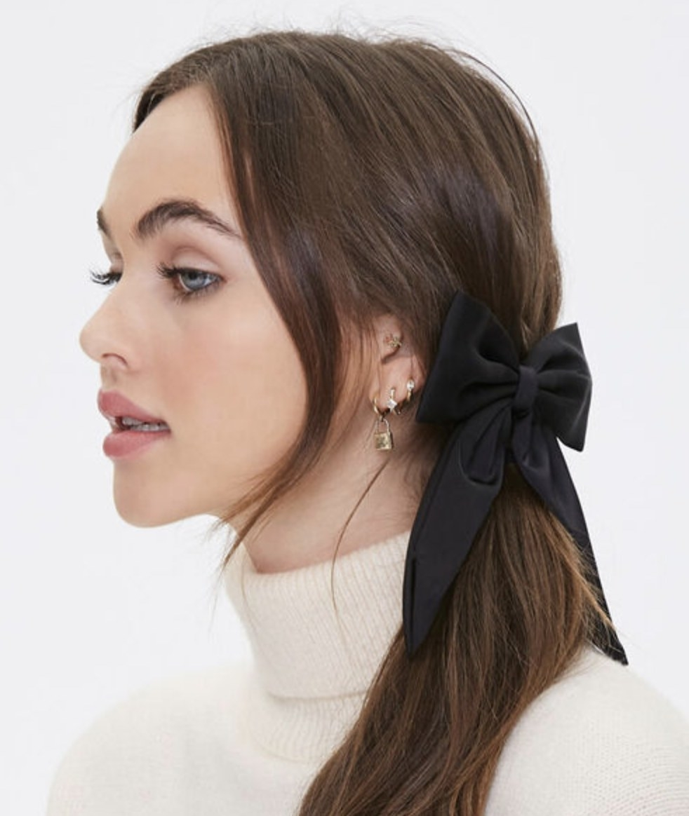 Model is wearing a black bow barrette hair clip in their hair with a white turtleneck
