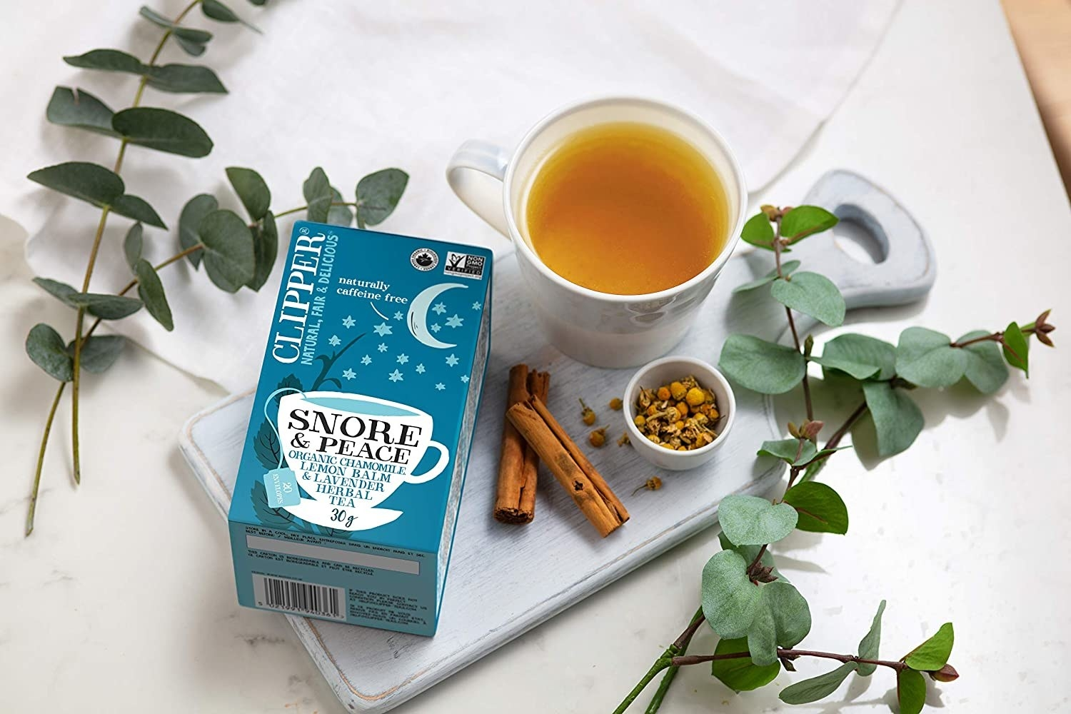 A pack of tea on a table beside herbs and a cup of tea