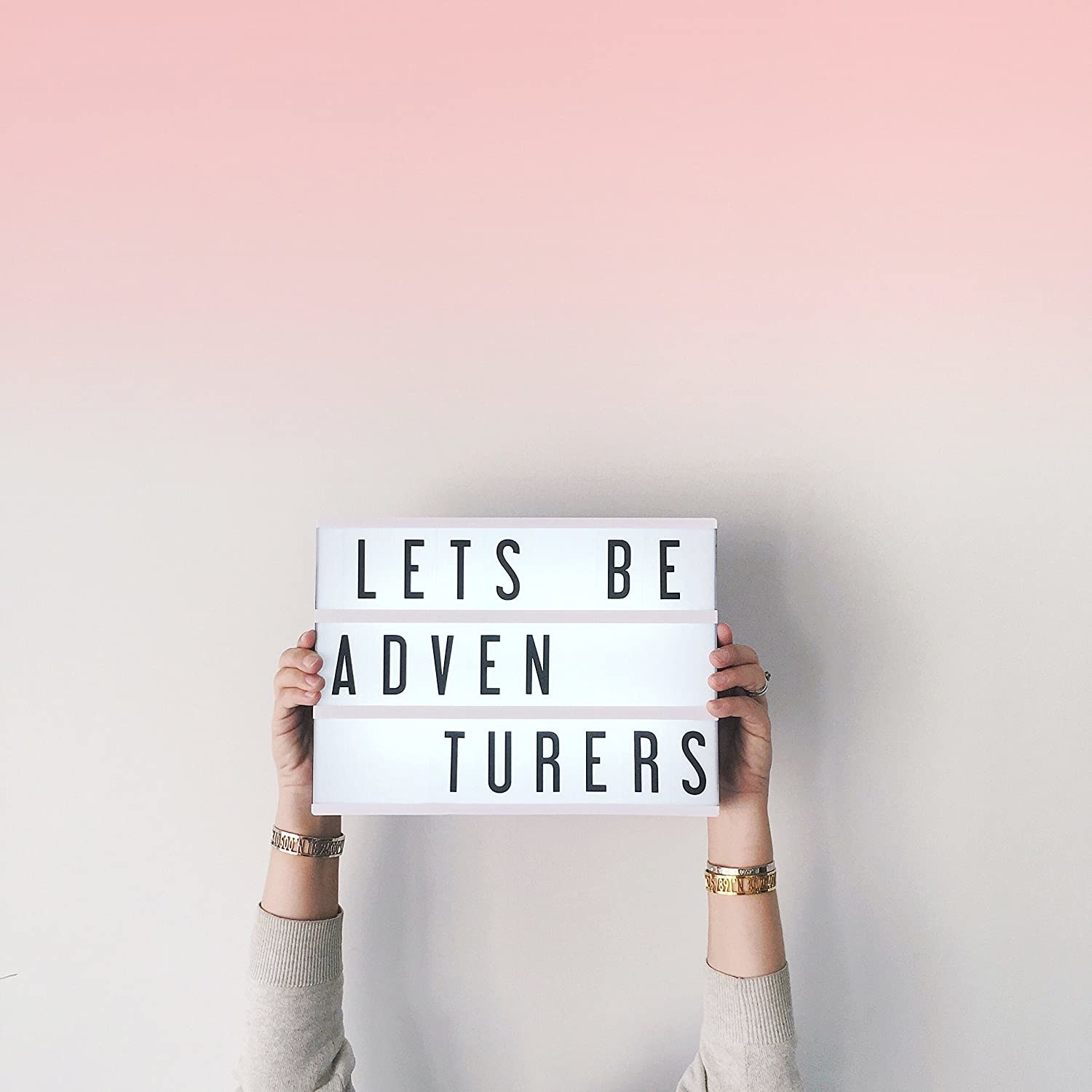 person holding up the box that says lets be adventurers