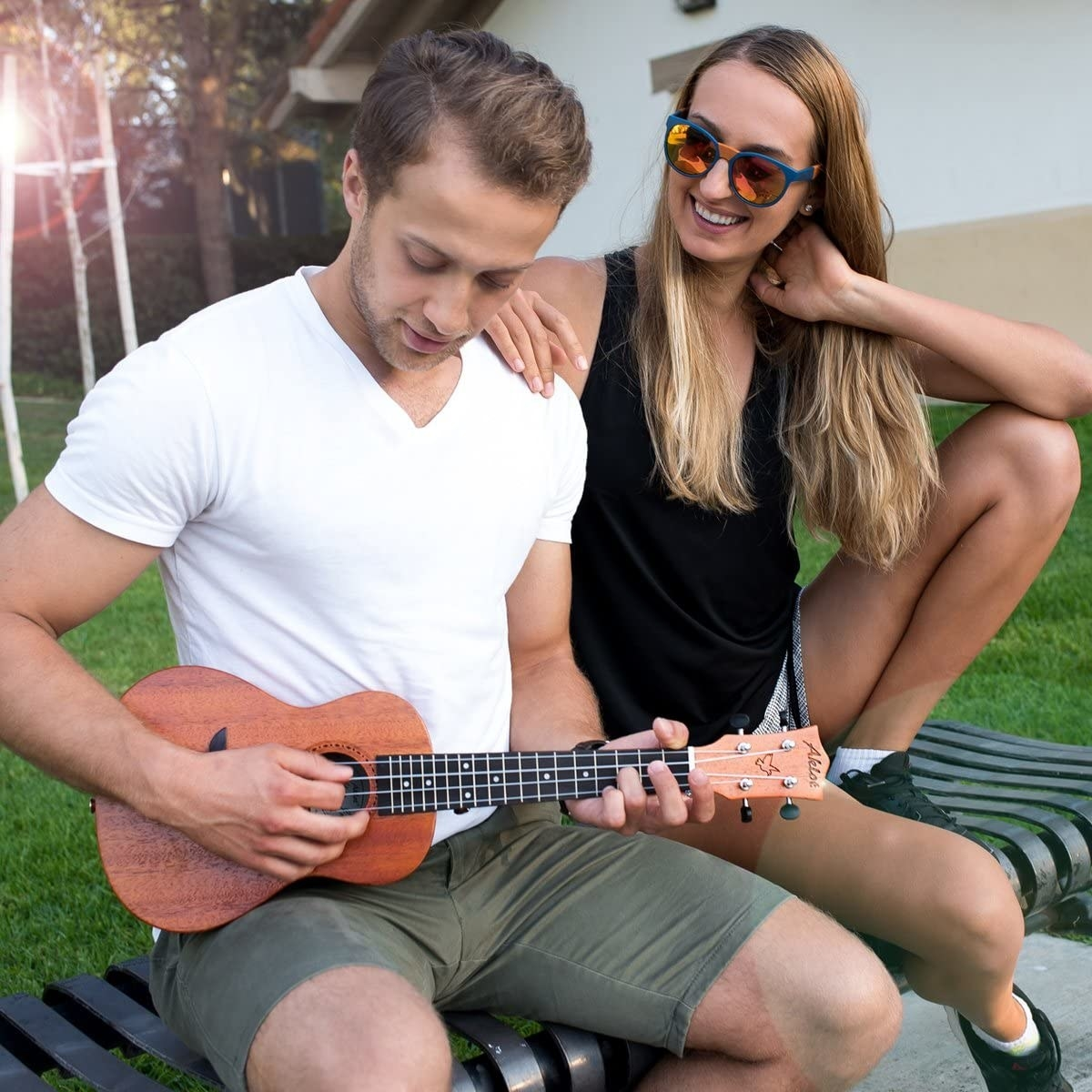 A person playing the ukulele for their friend in a park