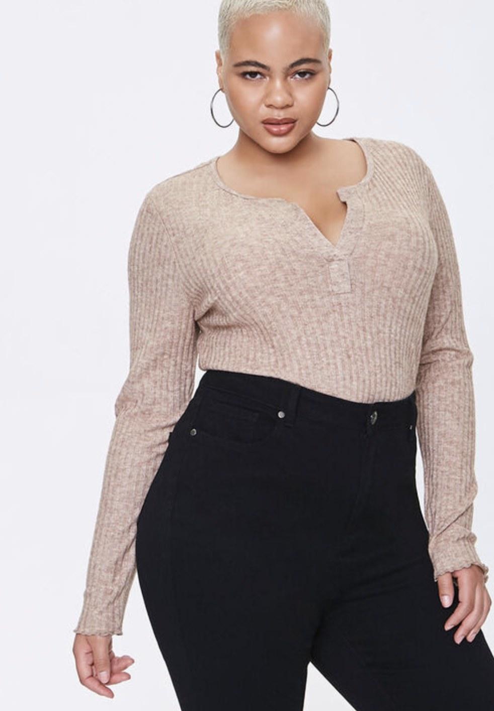 Model is wearing a beige bodysuit with black pants