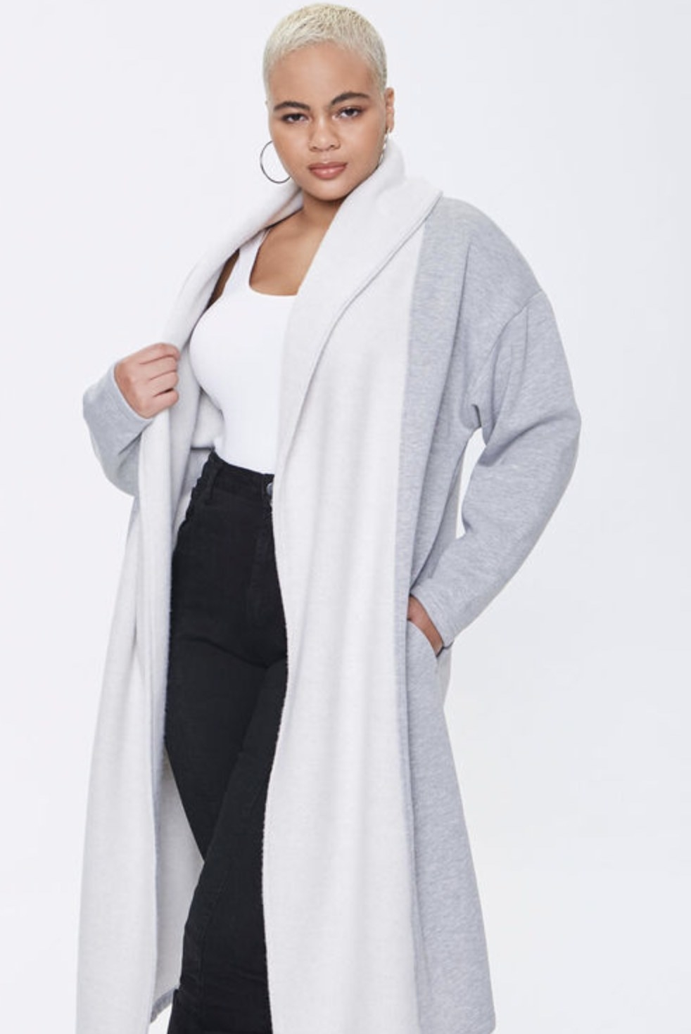 Model is wearing a white and grey long coat, white top, and black pants