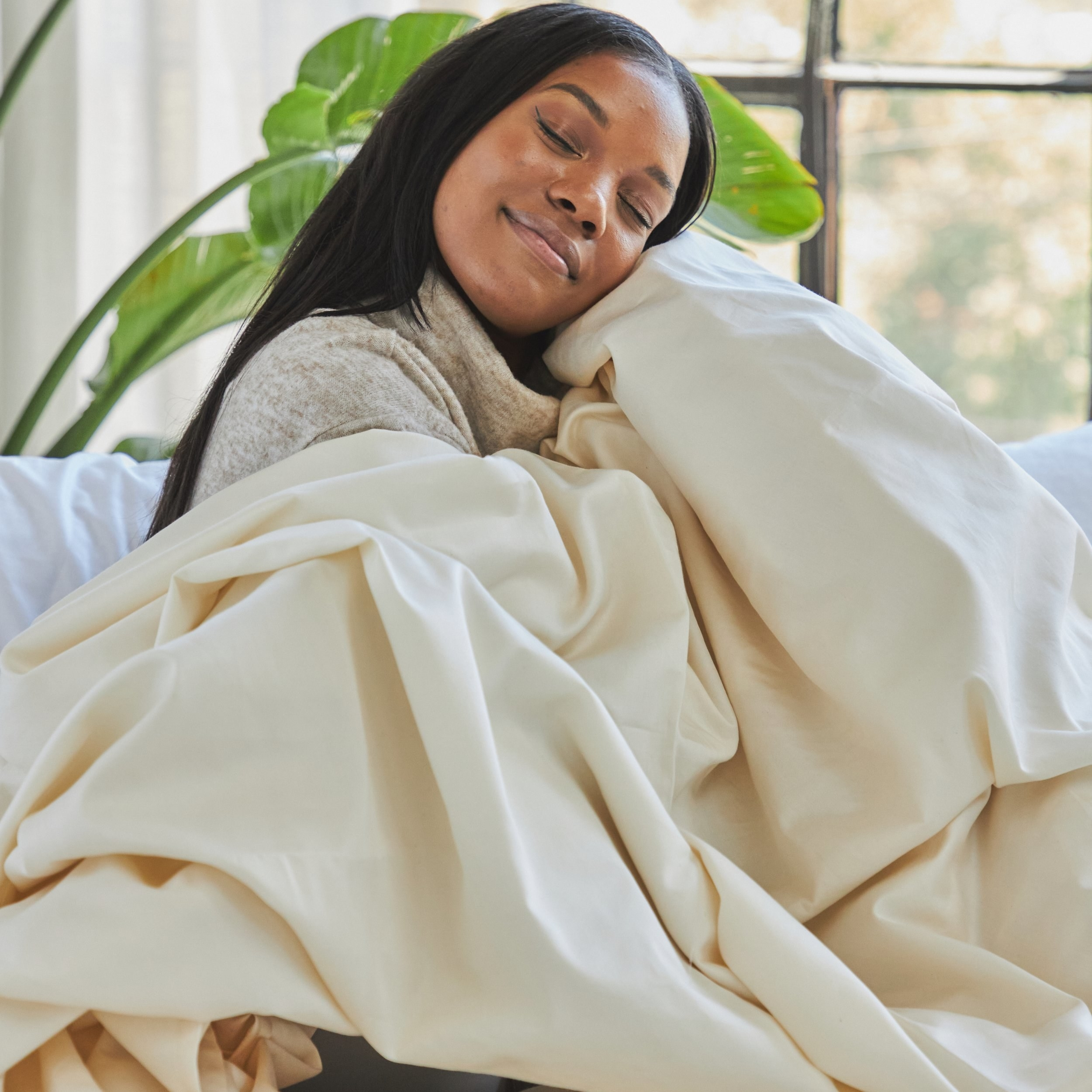 a model sits up on a bed snuggled up in the natural colored organic cotton sheets