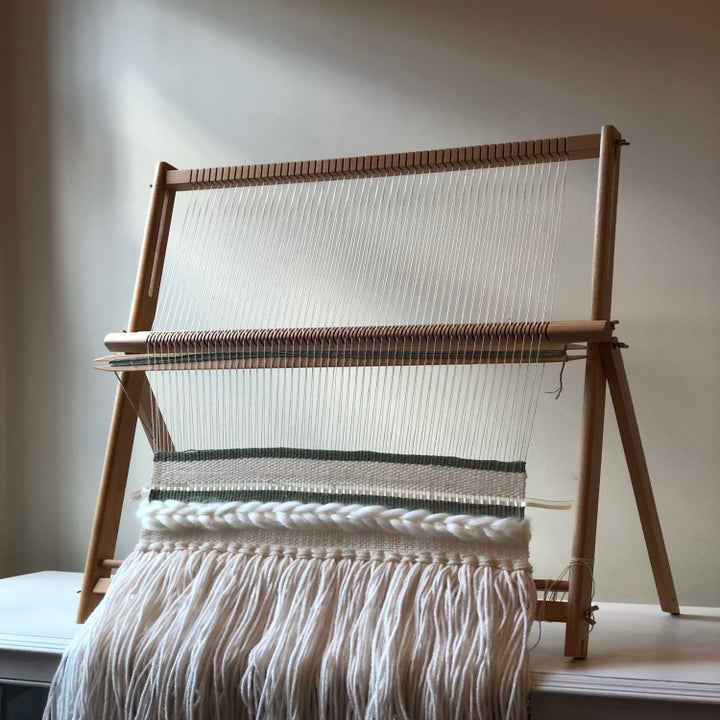A shot of the loom, heddle bar, and shuttle in use