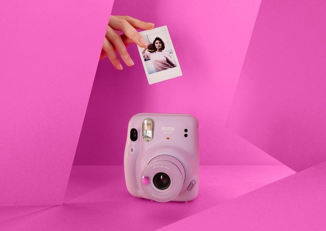 An instant camera with a person's hand holding a photograph above it