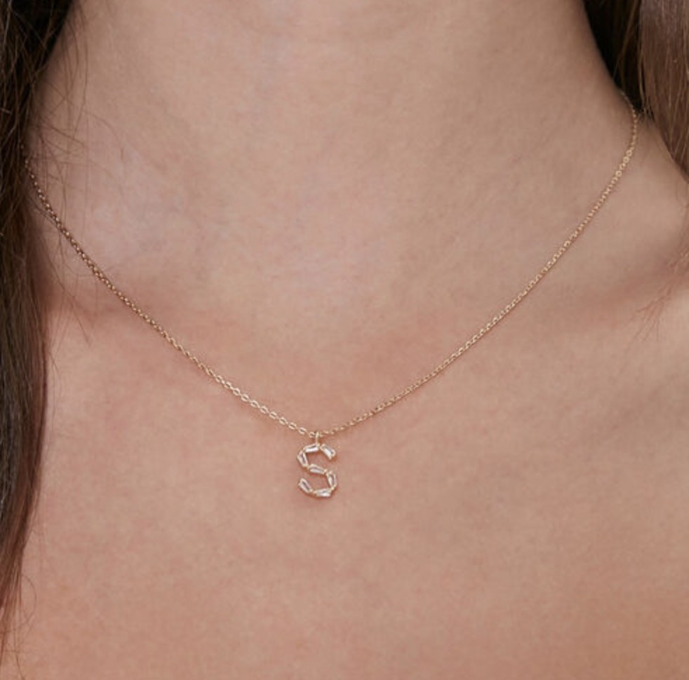 Model is wearing a gold necklace with an S pendant