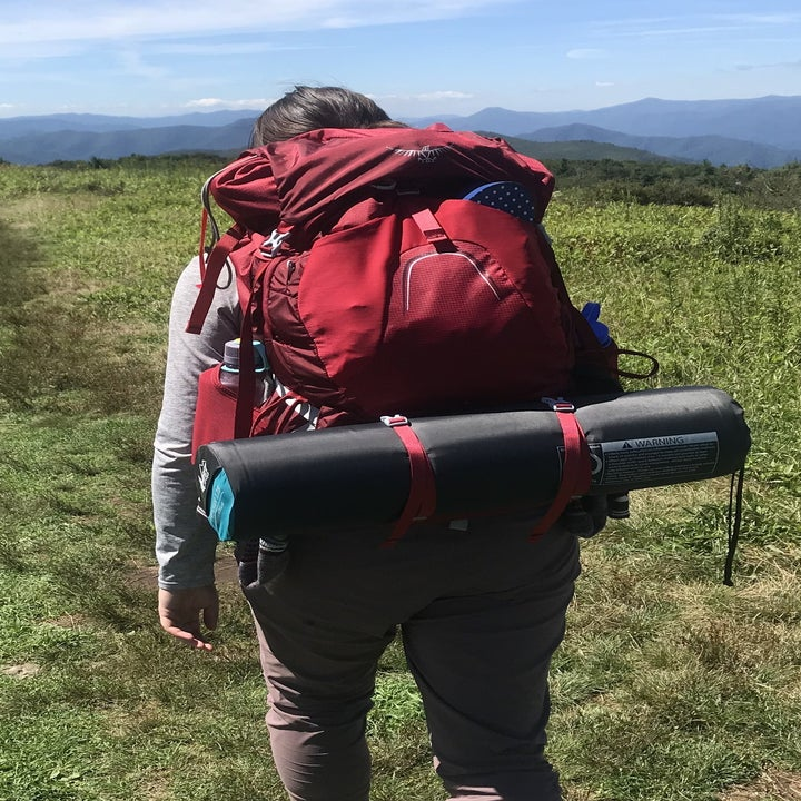 the writer walking in the pack with a sleeping mat strapped to it