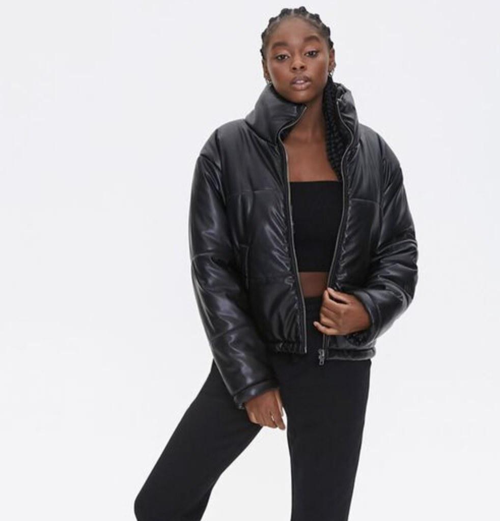 Model is wearing a black puffer jacket, black top, and black pants