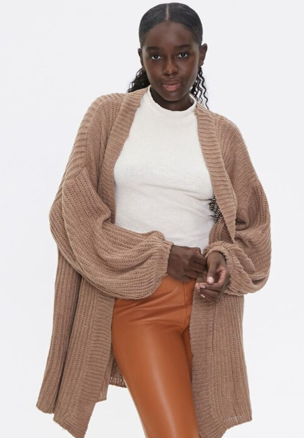 Model is wearing a tan cardigan, white top, and orange pants
