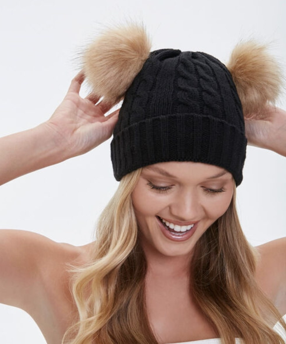 Model is wearing a black beanie with two big pom poms