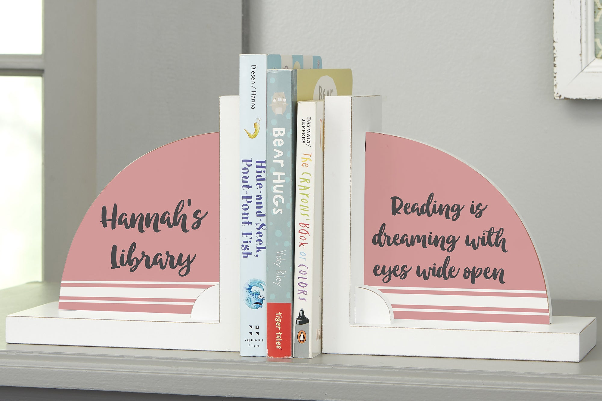 """the bookends in pink, one reads """"hannah's library"""" and the other reads """"reading is dreaming with eyes wide open)"""