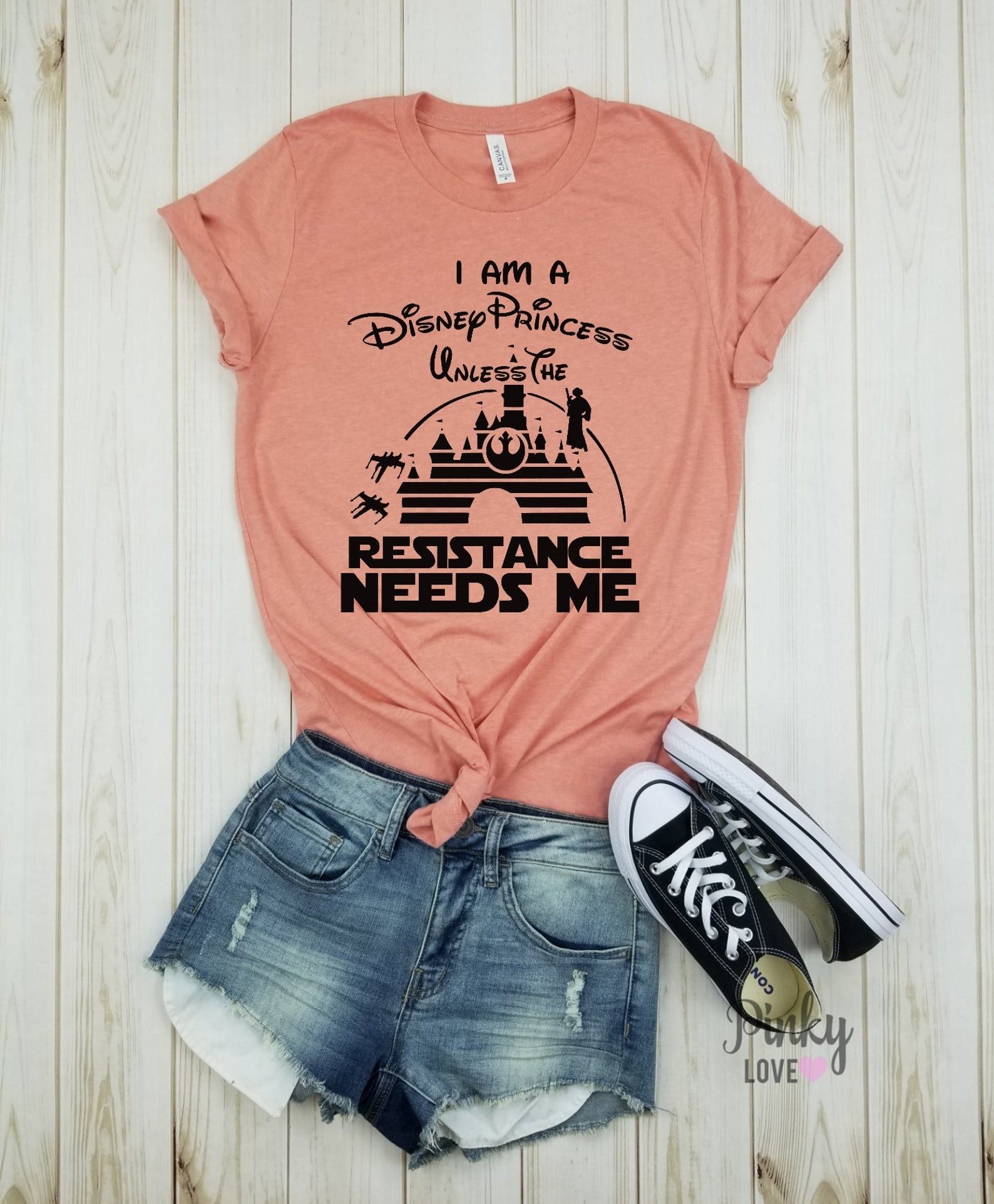 "pink T-shirt that says ""I am a Disney Princess unless the Resistance needs me."" Part of the quote is in the iconic Disney font while the rest is the starker Star Wars font. The Disney castle silhouette is on it also with a shadow of Princess Leia."