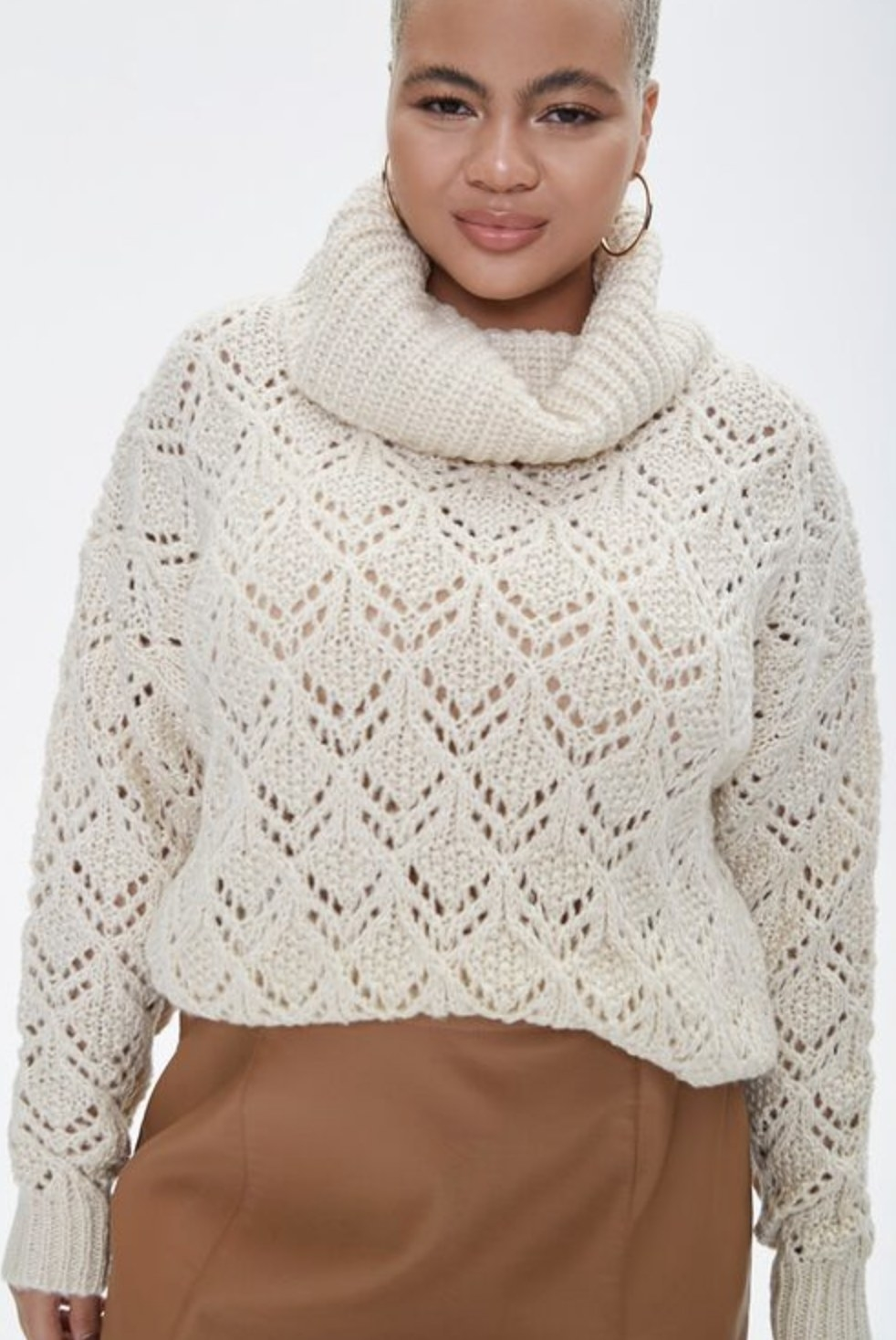 Model is wearing a white turtleneck sweater and a tan skirt
