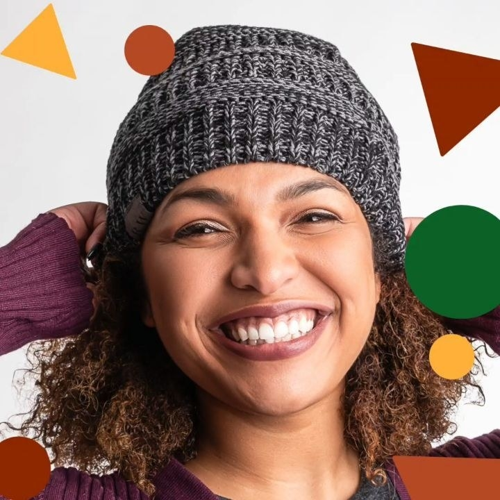 A person pulling the satin-lined beanie onto their head
