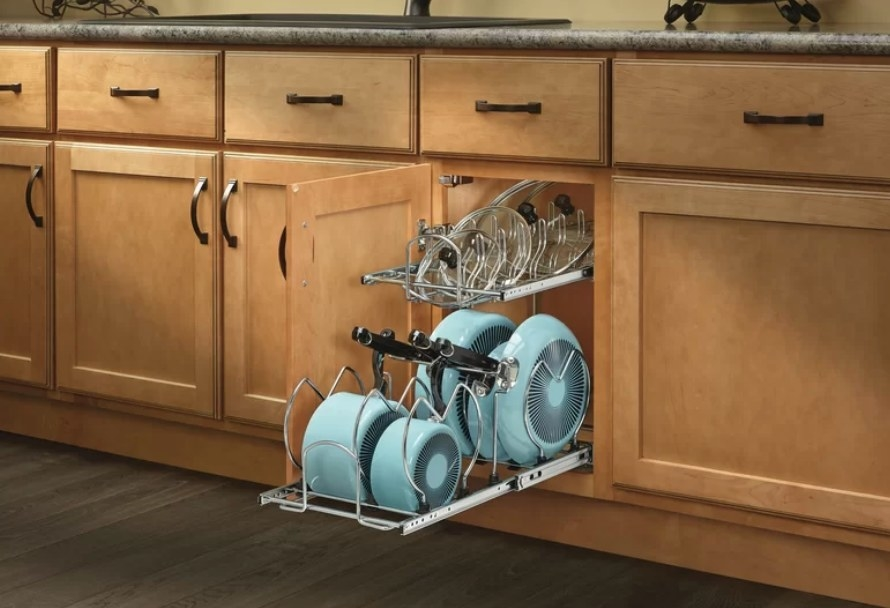 Metal kitchen divider unit in cabinet holding blue pots and pans