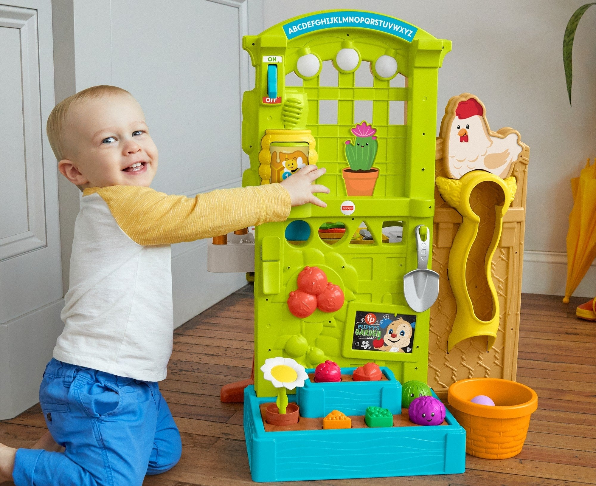 child playing with a fisher-price play garden
