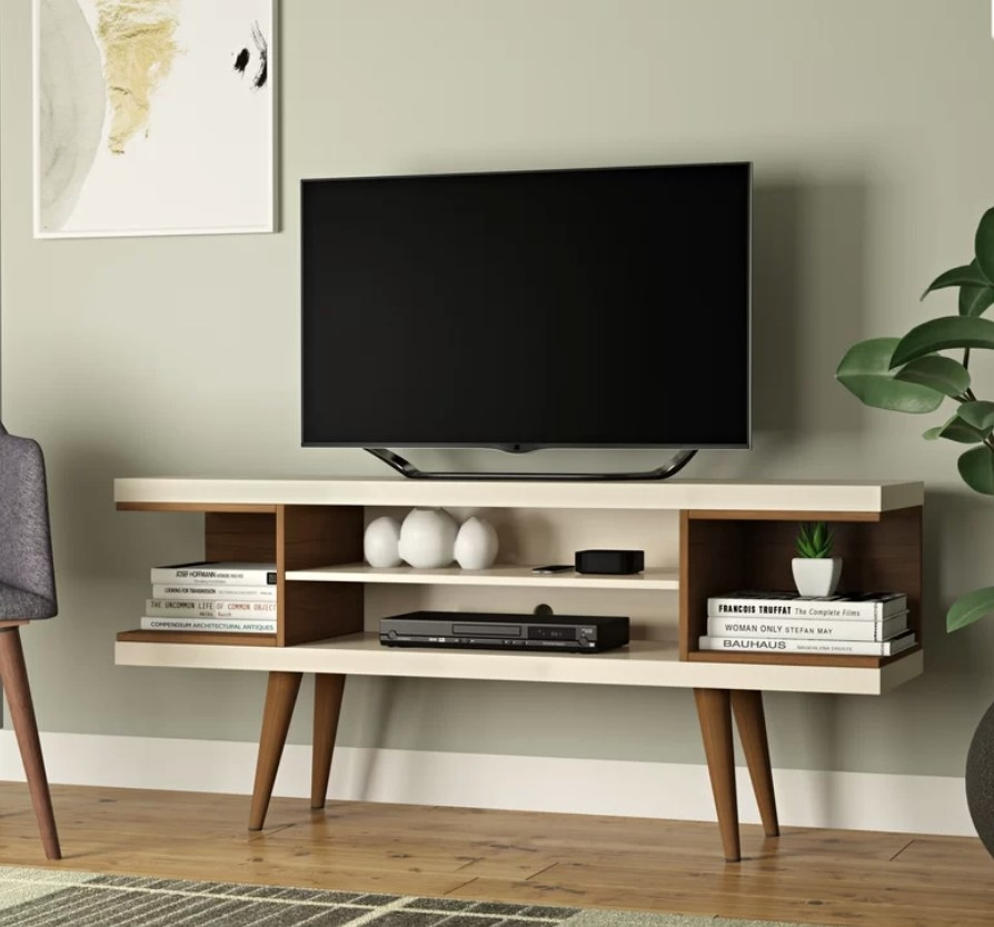 TV stand with brown wooden legs and off-white base with wooden shelf accents