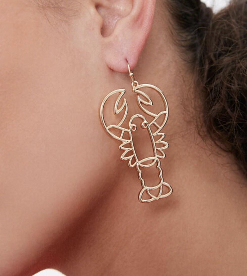 Model is wearing gold lobster cut-out earrings