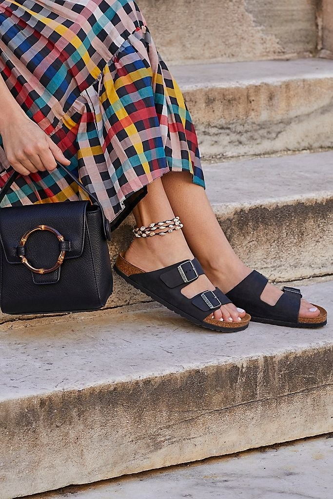 A model wearing the two-strap arizona birkenstocks in black with their cork foootbed