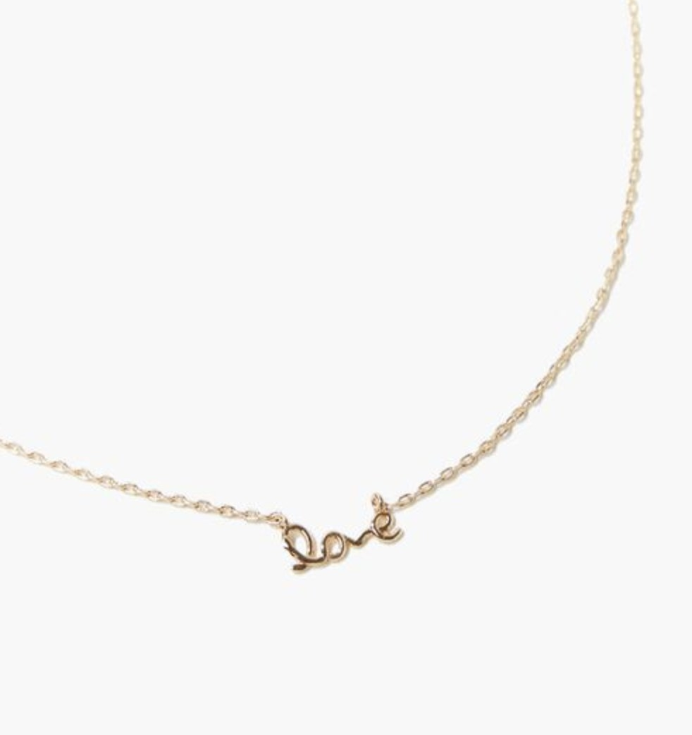 """A gold necklace with a pendant that says """"love"""""""