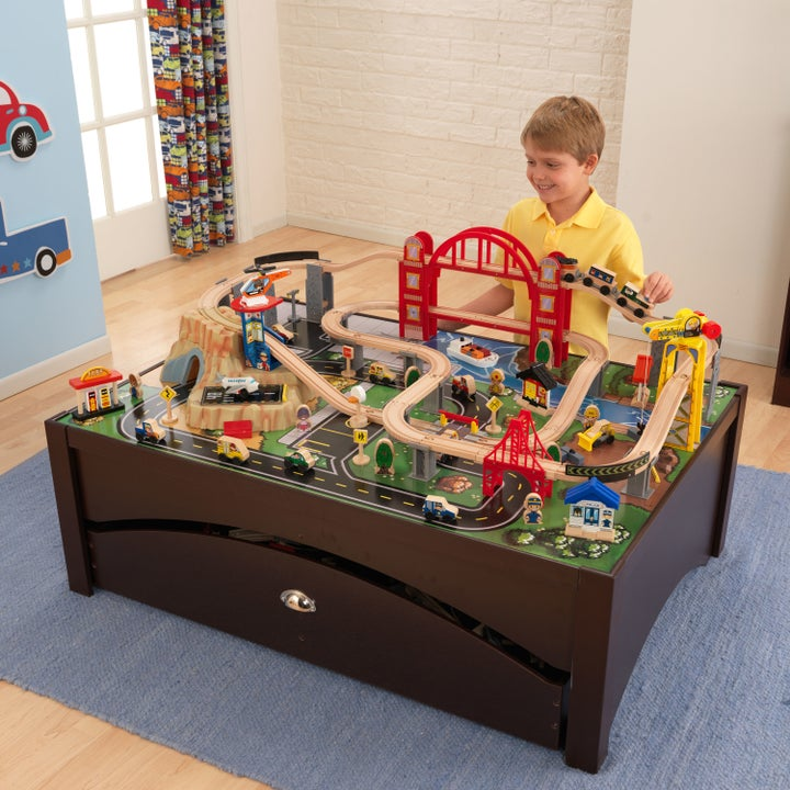 child playing with a toy train set on a wooden table