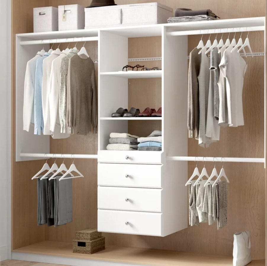 White closet system with white dresser, four hanging racks and center cabinets