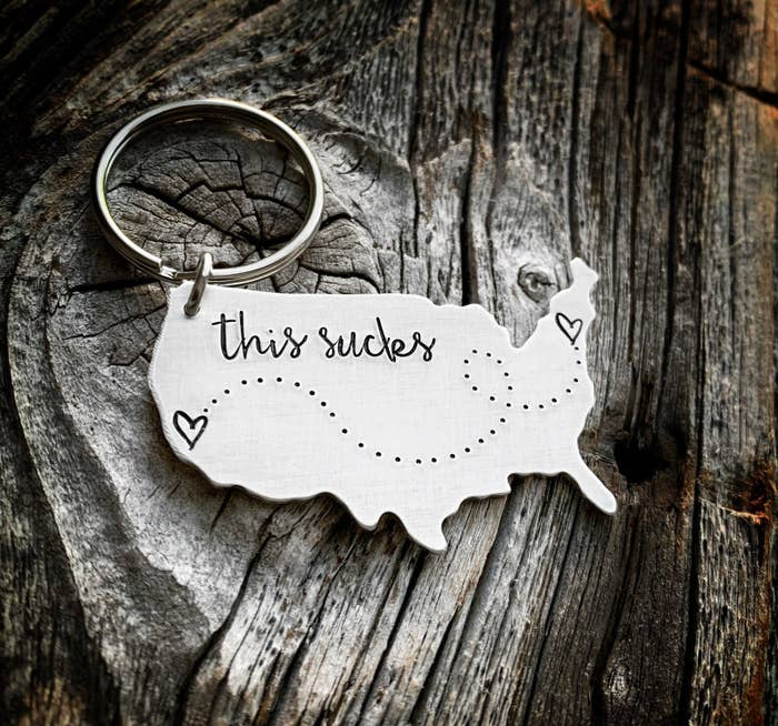 """A silver keychain in the shape of the United States with the words """"this sucks"""" engraved on it and two hearts on either side of the map"""