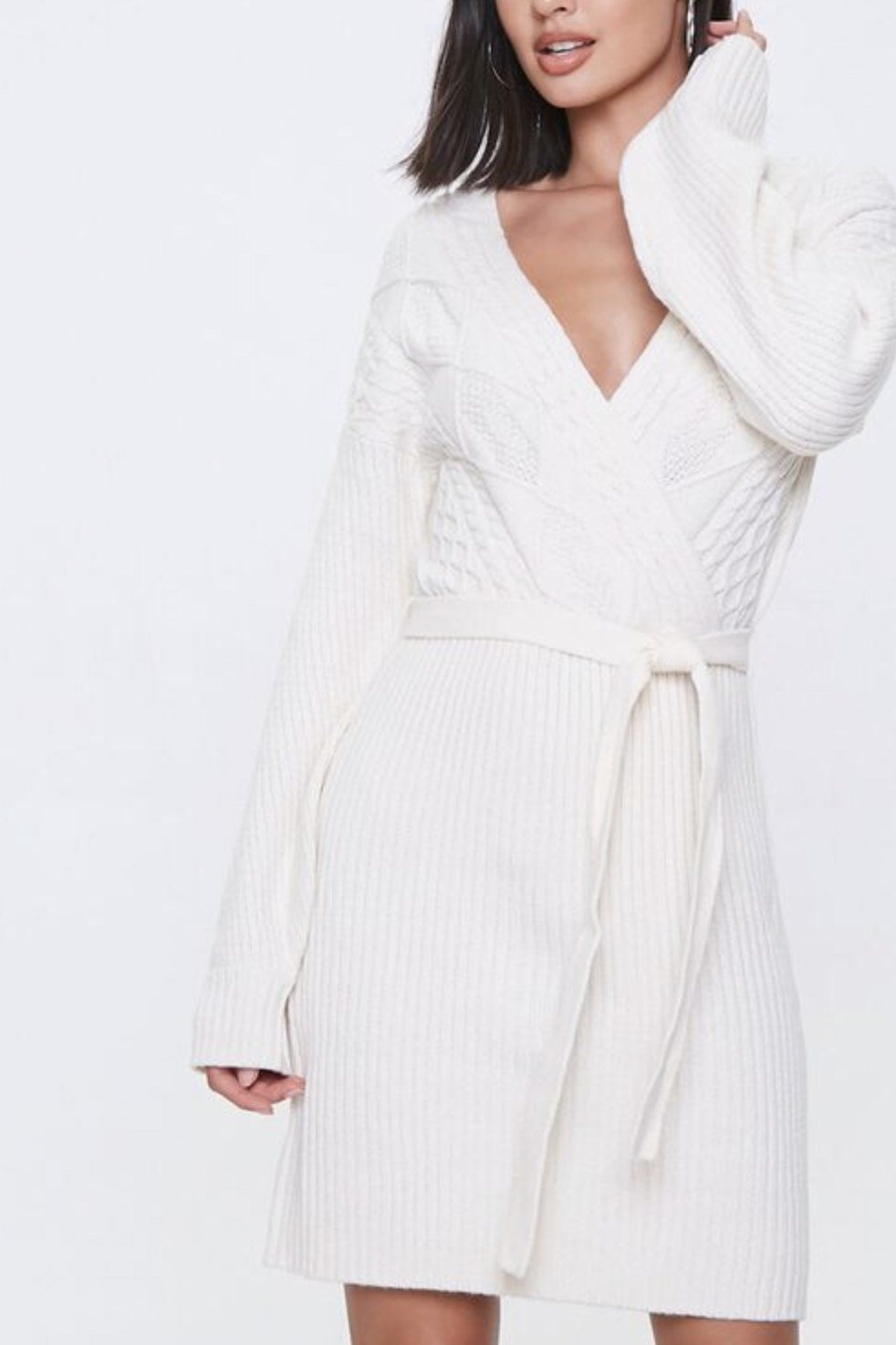 Model is wearing a white cable knit wrap dress