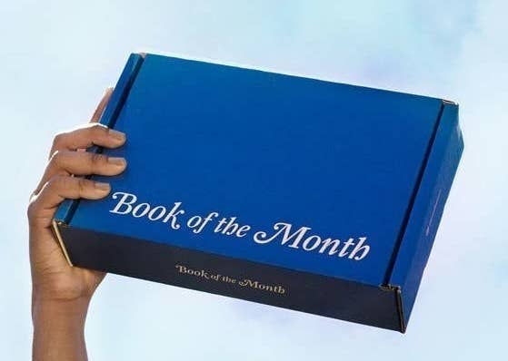 A person holding the blue book of the month box