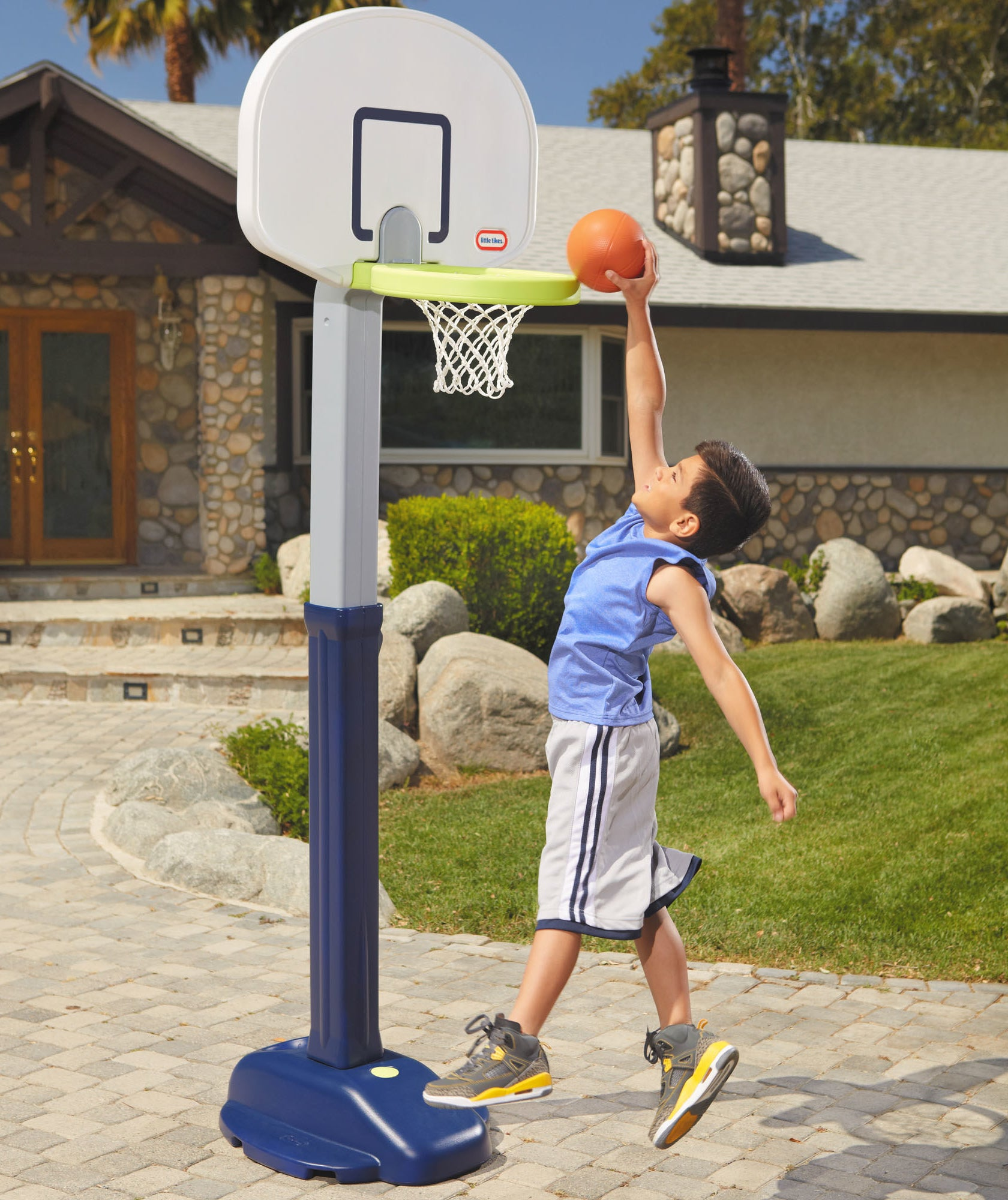 child slam dunking a small basketball into a little tikes basketball hoop