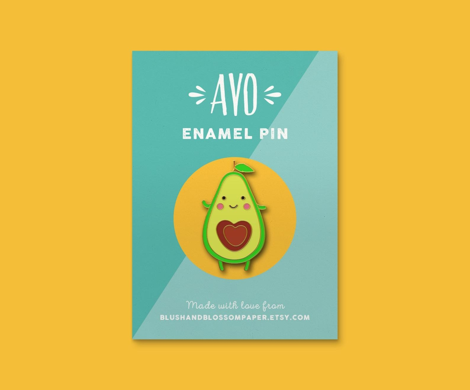the avocado enamel pin against a yellow background