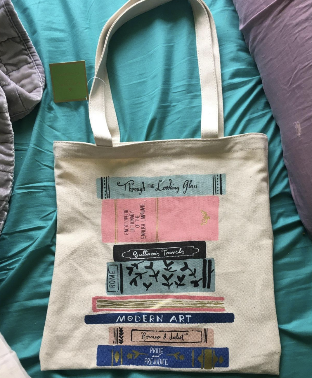a reviewer photo of the tote bag with various kinds of books printed on the outside with classics like romeo & juliet and pride & prejudice