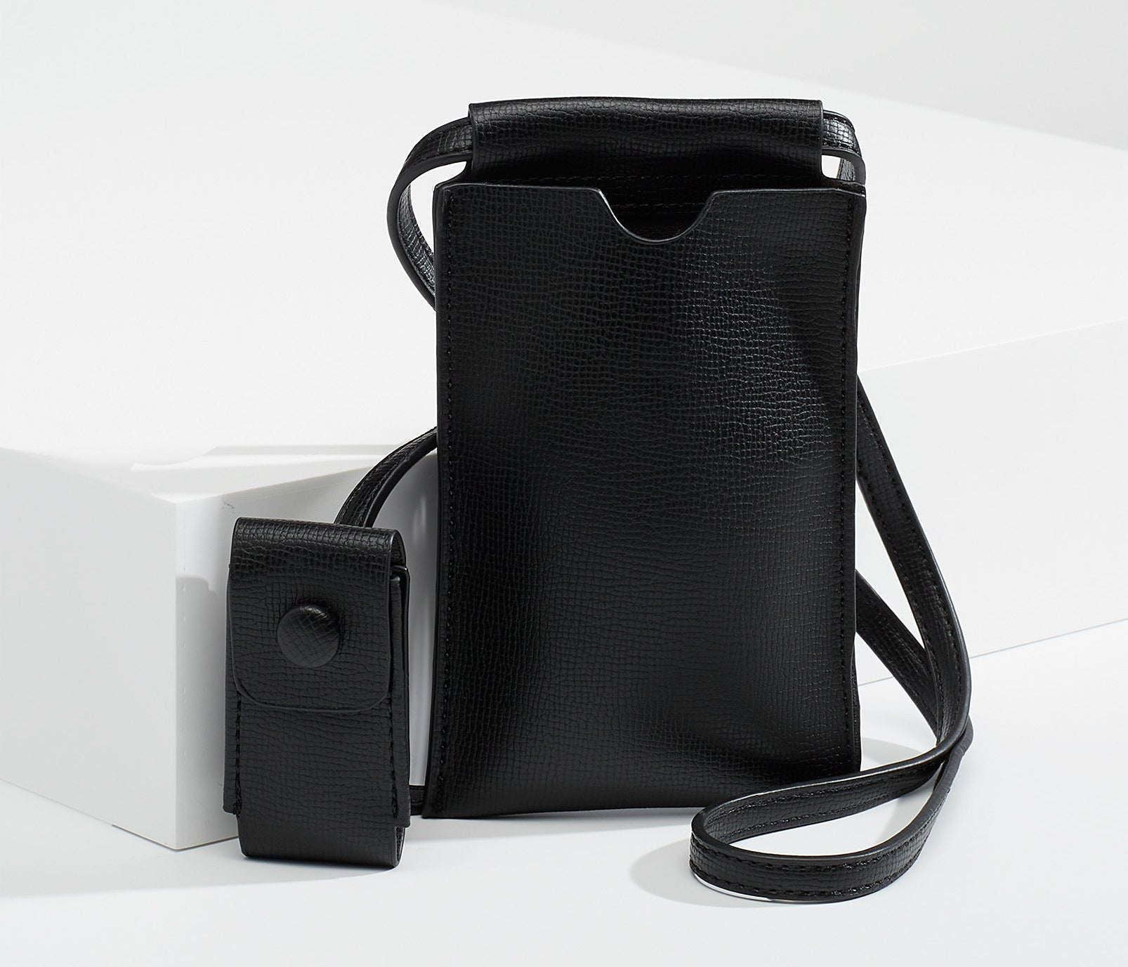 A small faux leather bag with a tiny sleeve on the strap for lip balm