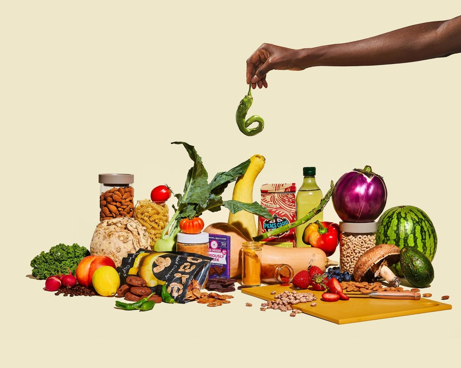 a hand plucks a pepper out of a pile of veggies and pantry staples