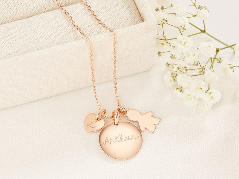 a gold necklace with a circular charm that says arthur, a boy charm, and a little heart with an L in it